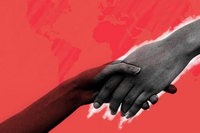 dwie trzymające się dłonie na tle mapy świata